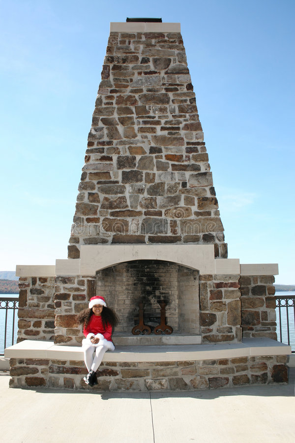 Girl and fireplace. A young girl sitting on the hearth of an outdoor fireplace royalty free stock photo