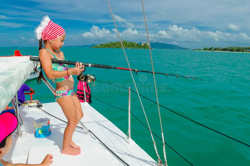 A girl is fishing on a boat. Colorful tropical pattern around.  stock photo