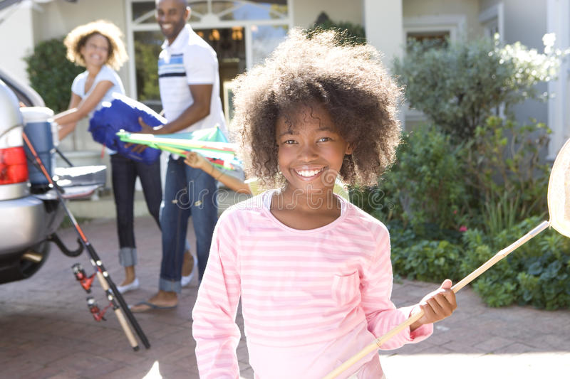 Girl (8-10) with fishing net in driveway, parents in background, smiling, portrait stock photo