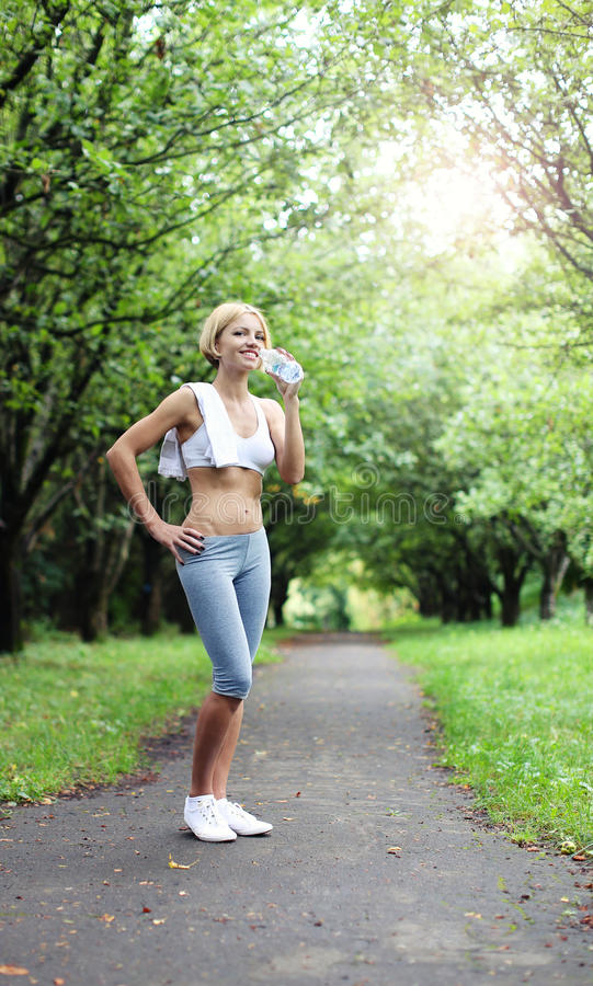 Girl with fit abdominal with bottle of water. Young beautiful woman wearing sport wear drinking water after jogging at green park. Model standing in the park stock photography