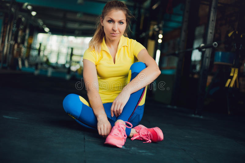 Girl in fitness club. Young female athlete sitting on floor and tied his shoelaces, ready to workout royalty free stock image