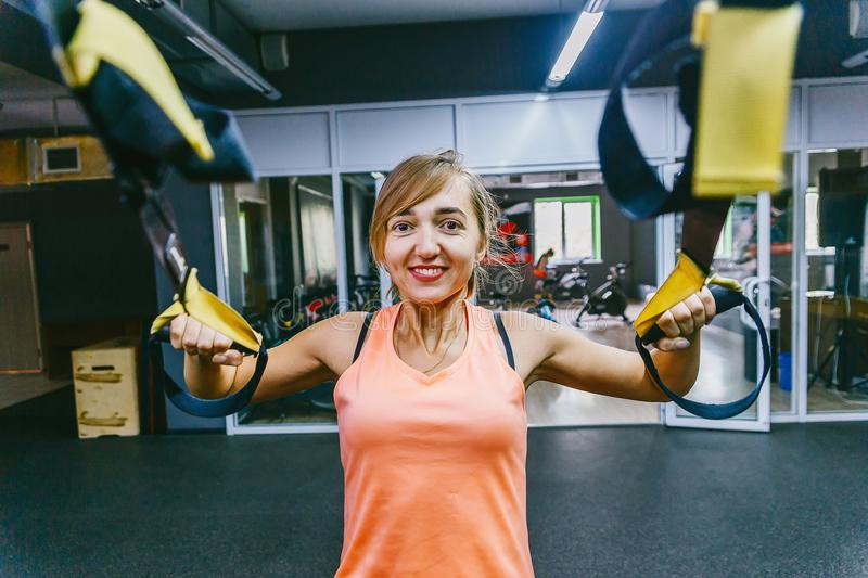 Girl in fitness hall with loops. sports training hinges TPX, suspension training. Strapping. Development of the vestibular apparat royalty free stock images