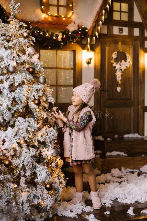 A girl of five or six years in winter pink clothes and ugg boots stands near the Christmas tree and decorates it with balls on the stock photography