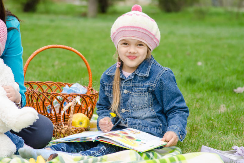 Girl of five years sitting on a green lawn stock photos