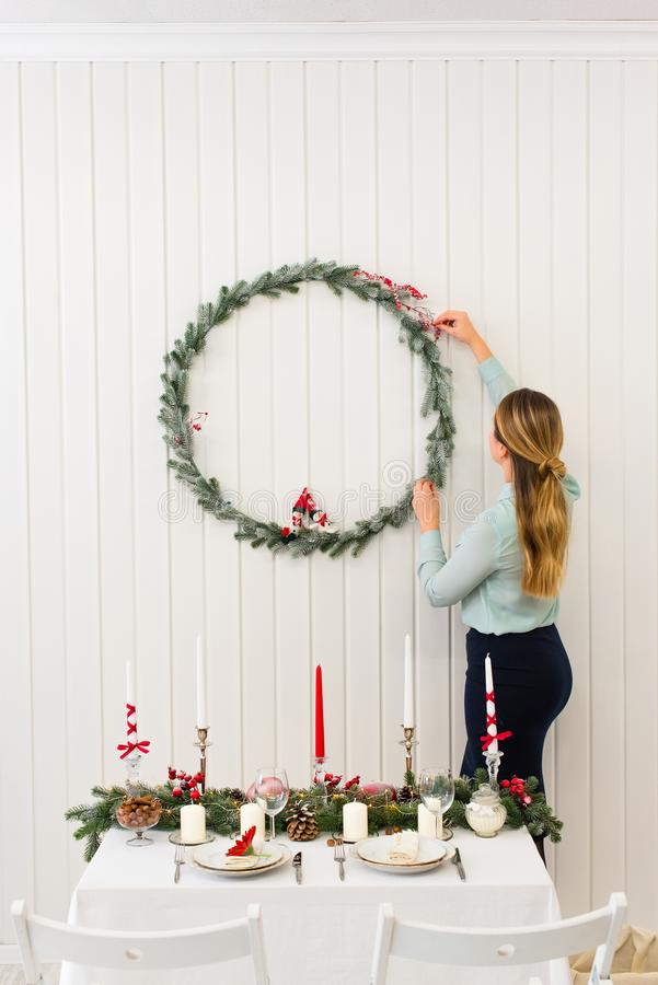 Girl fixing New Year decoration on the white wall royalty free stock images
