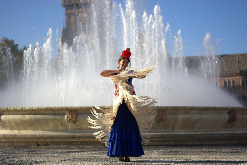 The happy woman dancing flamenco near the fountain in summer. The beautiful girl dressed as flamenco royalty free stock images
