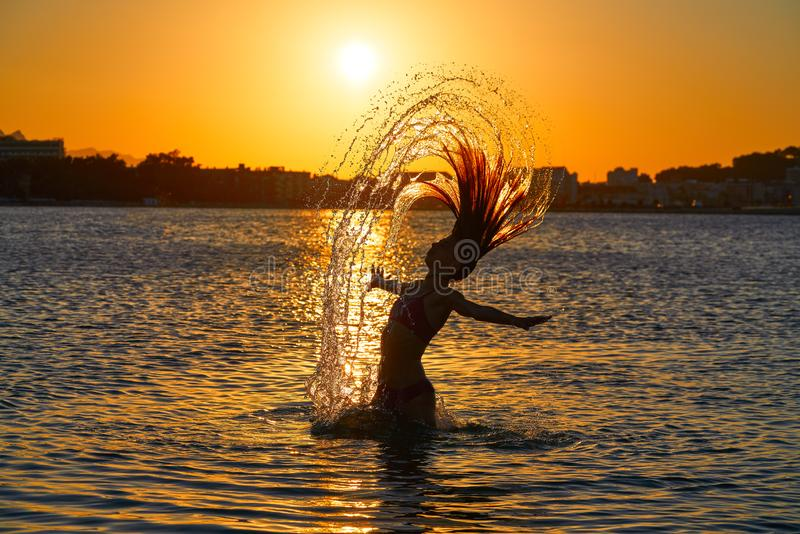Girl flipping hair flip at sunset beach stock photography