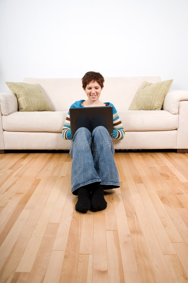 Girl on the floor. Woman cute sitting on the floor with laptop