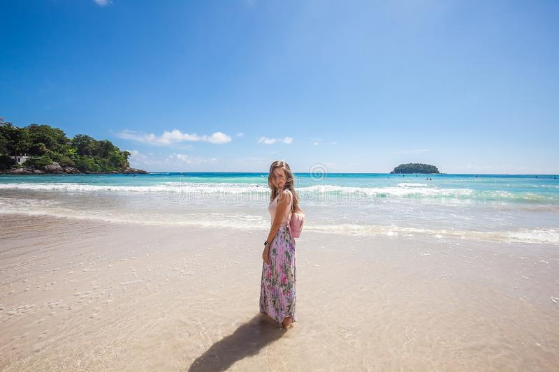 Girl in floral pink maxi skirt walking on the sea shore. Girl wearing floral pink maxi skirt and backpack walking barefoot on the sea shore while sky is royalty free stock photos