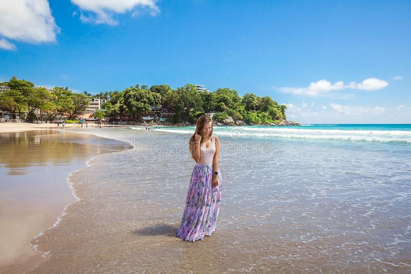 Girl in floral pink maxi skirt walking on the sea shore. Girl wearing floral pink maxi skirt walking barefoot on the sea shore while sky is incredible blue royalty free stock photography