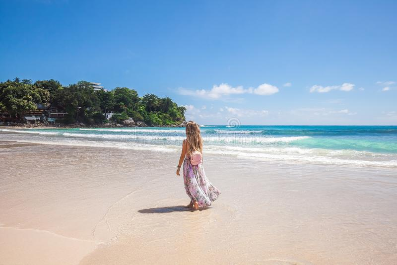 Girl in floral pink maxi skirt walking on the sea shore. Girl wearing floral pink maxi skirt and backpack walking barefoot on the sea shore while sky is stock photo
