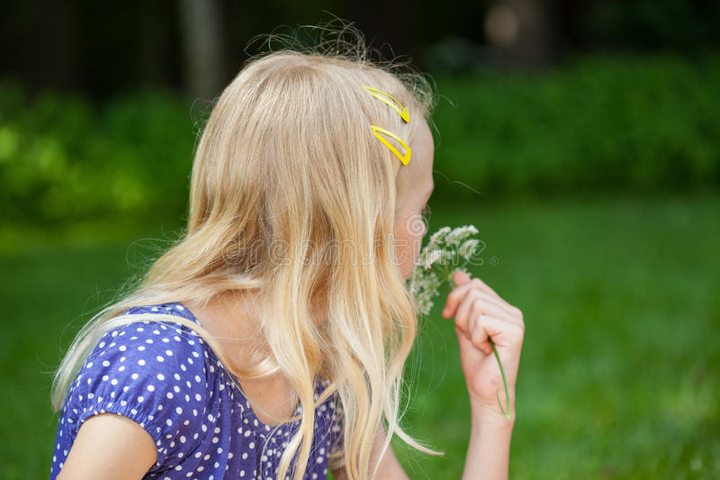 A girl with a flower. A blonde girl holding a white flower stock photo