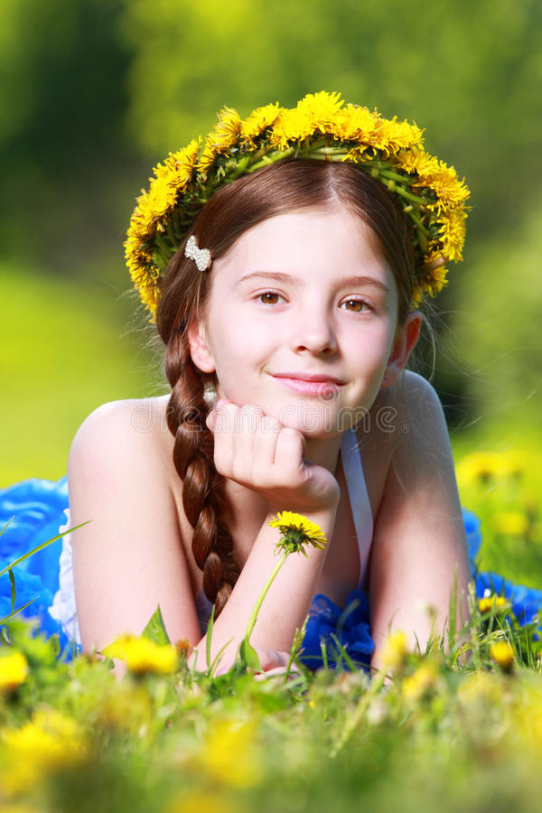 Girl with flower crown. Pretty young girl, wearing a dandelion flower wreath or garland or crown around her head royalty free stock images