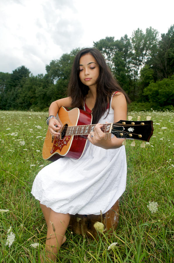 Download Girl In Flower Field Playing A Guitar Stock Photo - Image: 20795180
