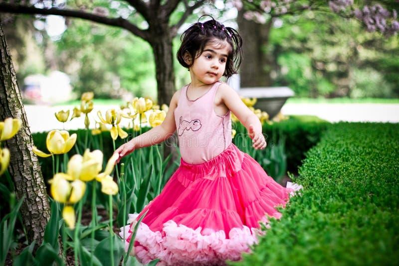 Girl in flower garden royalty free stock image