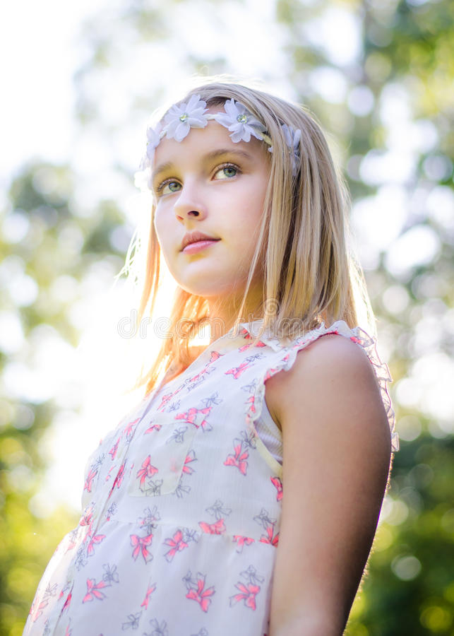 Girl with flower headband. Girl in summertime with leaves in background wearing a flower headband looking off in the distance stock photo