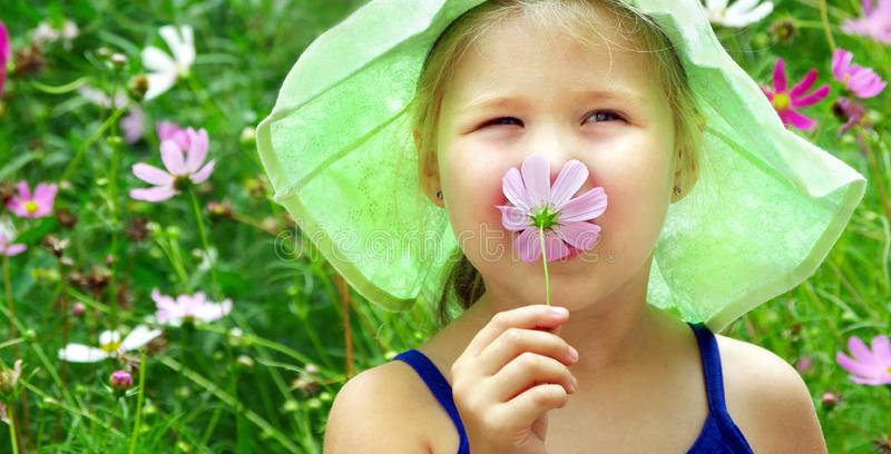 girl with a flower in her hand. child among the flowers. pollen allergy royalty free stock photography