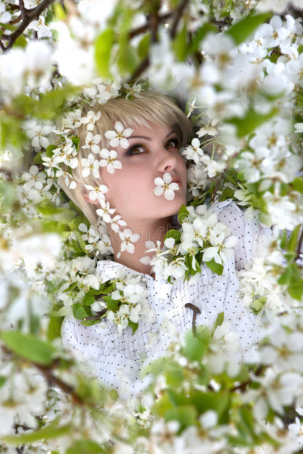 Girl among flowering apple tree stock photography