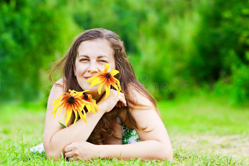 Girl with flowers lays in park royalty free stock photo