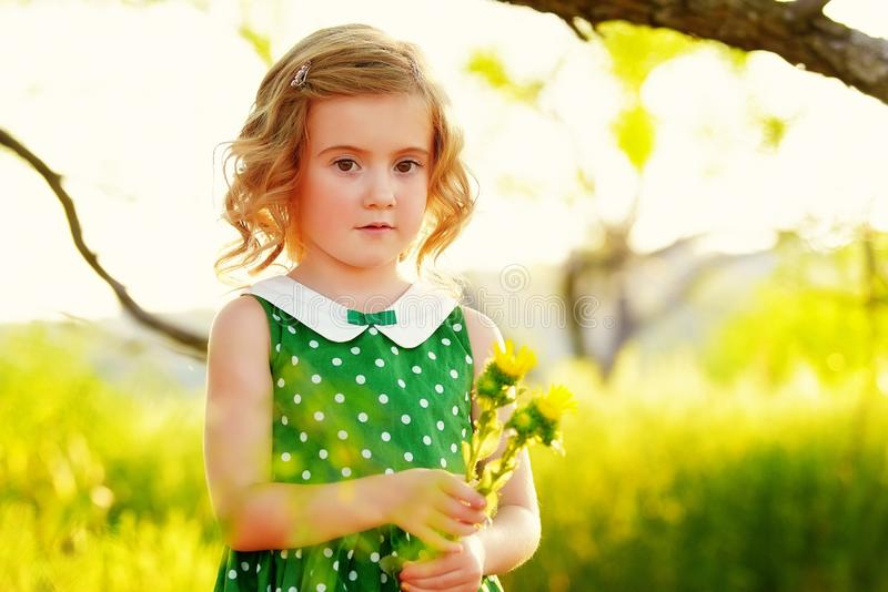 Girl with flowers. Pretty blonde girl in green polka dot dress with white collar, under branch of tree holding wild flowers in Springtime stock photos