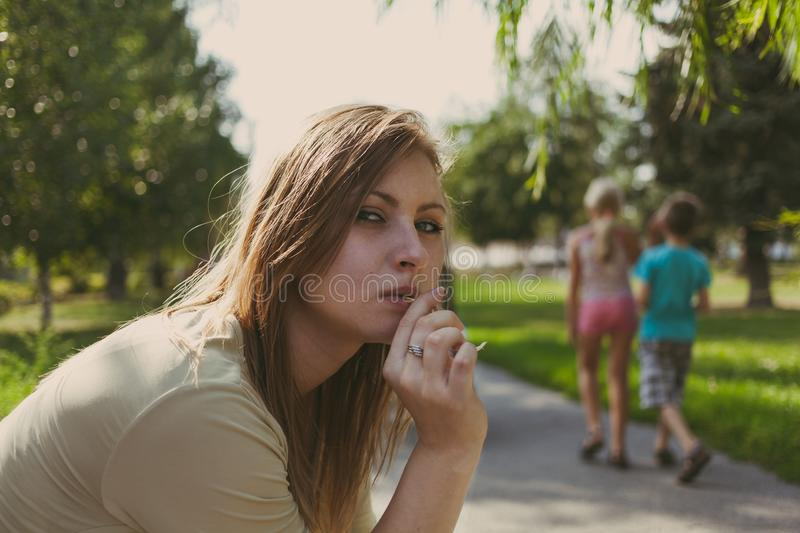 Girl with flowing hair chewing a blade of grass stock image