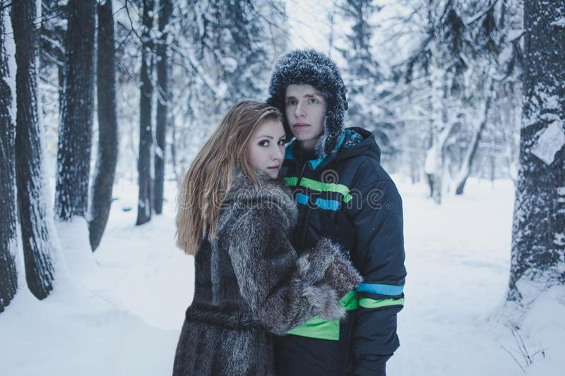 Girl with flowing hair in a gray coat and a guy in a black jacket and hat against the background of the winter forest royalty free stock image