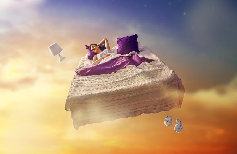 Girl is flying in her bed. Woman`s dreams. Pretty girl is flying in her bed trough star sky stock image