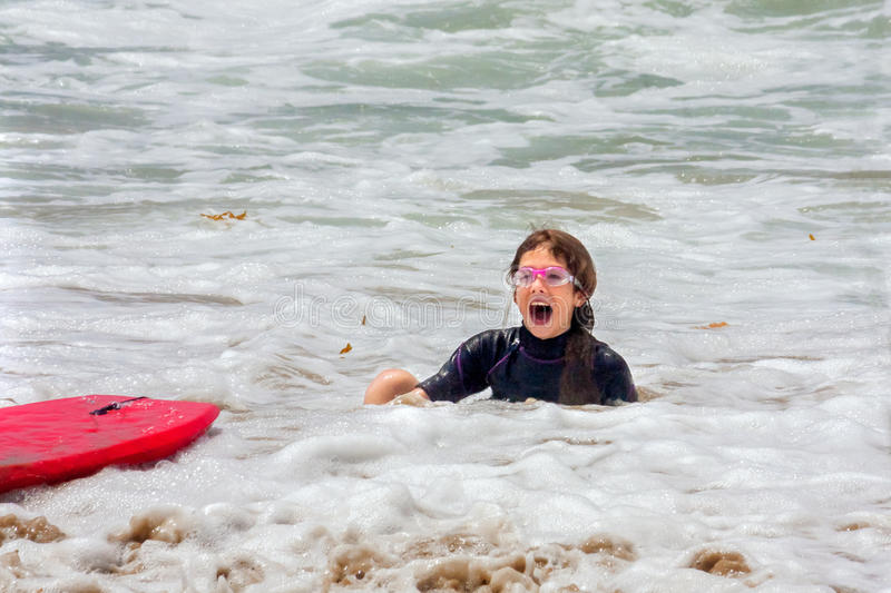 Girl in Foamy Ocean Water With Goggles. A young girl sits with an open mouth, surprised look in shallow, foamy, ocean water after she fell off her boogie board royalty free stock images