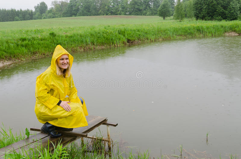Girl on foot bridge to pond with yellow rain coat stock photography