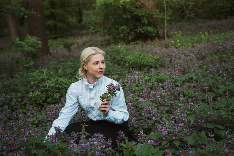 Girl in the forest collects herbs. Girl in vintage clothes in the forest collects herbs royalty free stock image