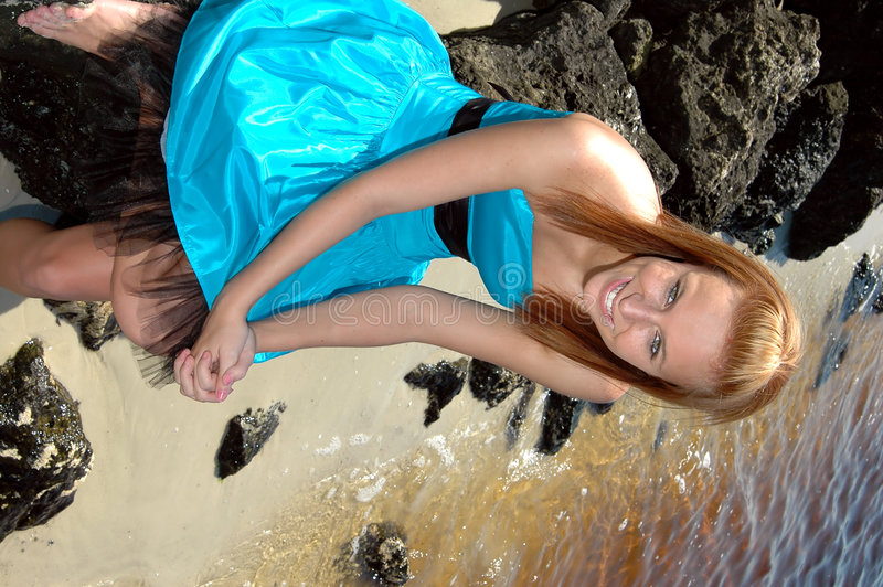 Girl in formal dress. A teen in her prom dress on the rocks at the beach stock photos