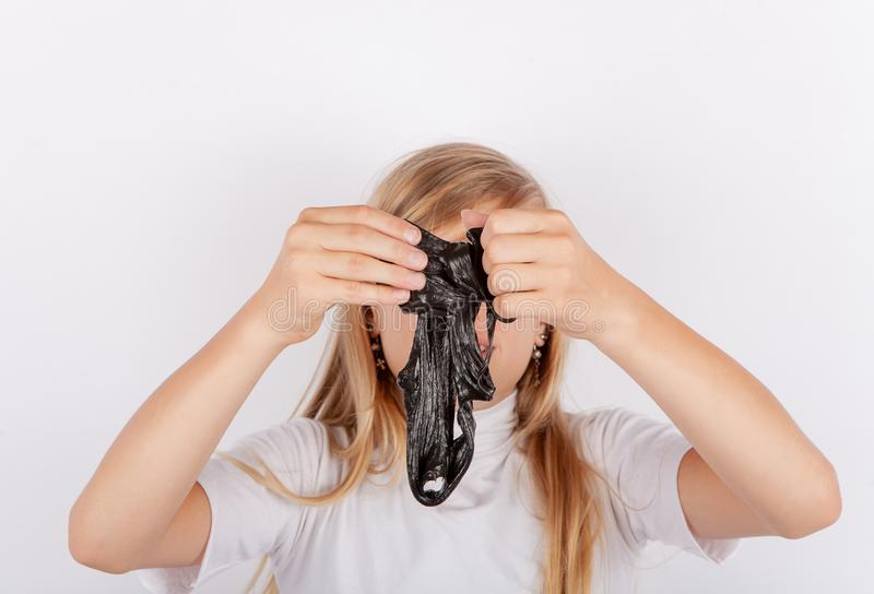 Girl squeezing a black slime in front of her face royalty free stock photography
