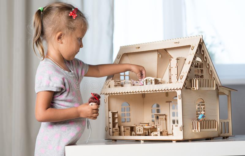 A girl playing with a dollhouse stock photos
