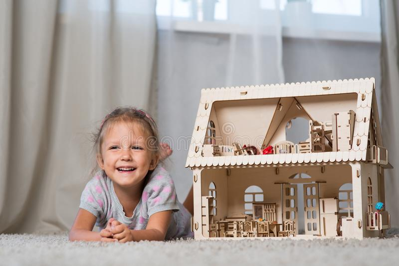 A girl playing with a dollhouse royalty free stock image