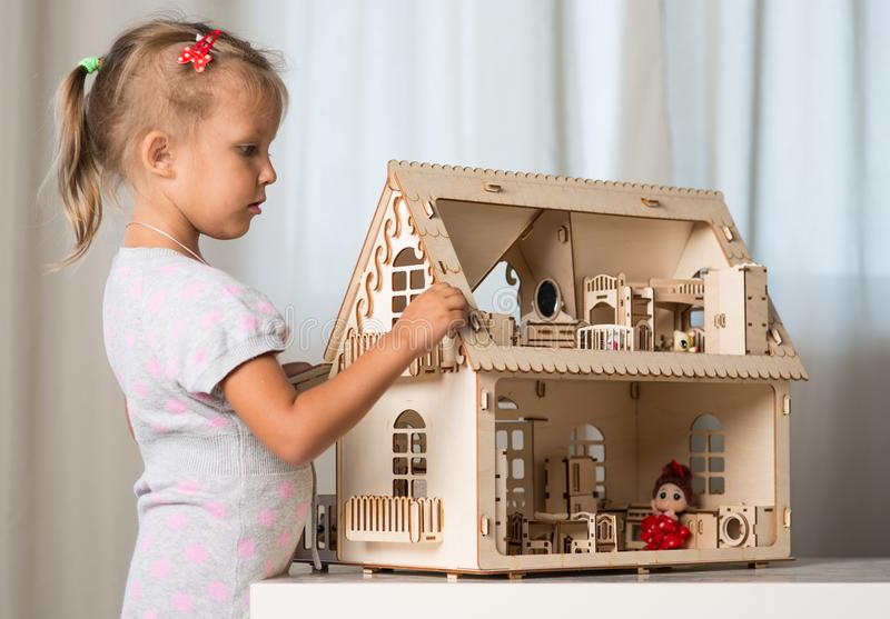 A girl playing with a dollhouse stock photography