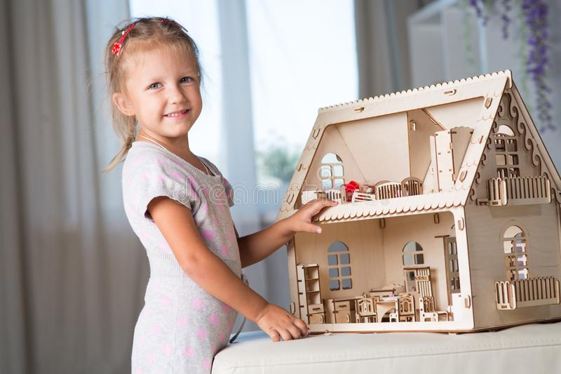 A girl playing with a dollhouse royalty free stock images