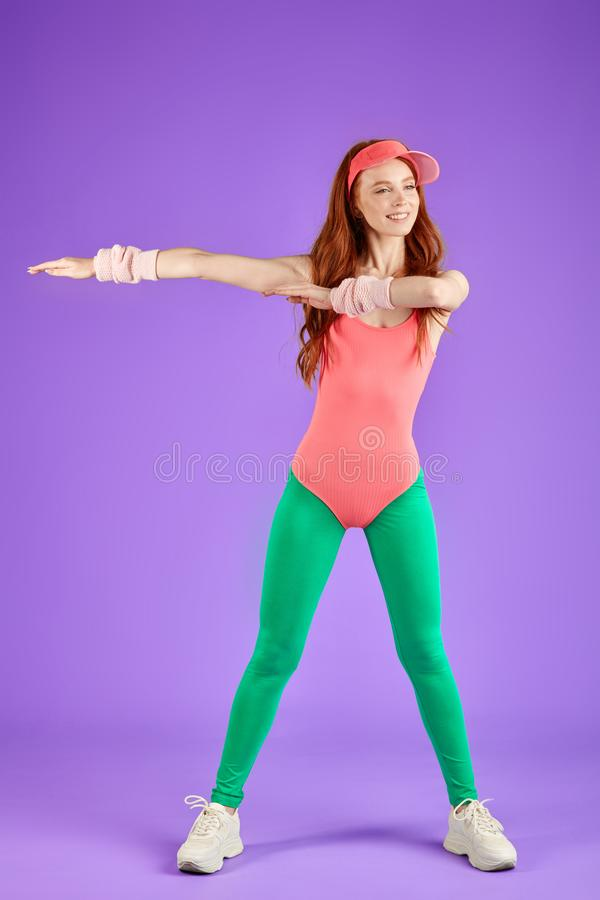 View of active red-haired fitness girl dressed in 80s style royalty free stock images