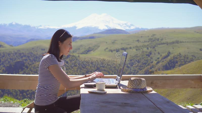 Girl freelancer working in a beautiful place in nature in the mountains. Girl freelancer working in a beautiful place in nature stock image