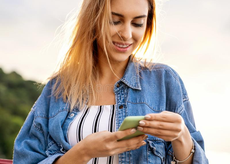 Girl freelancer working with phone at sunset stock photos
