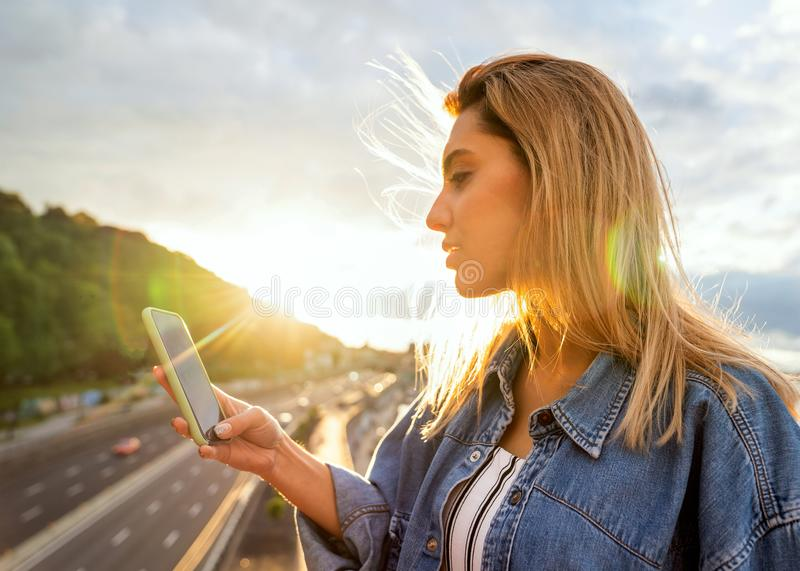 Girl freelancer working with phone at sunset stock image
