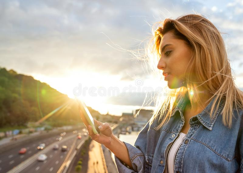Girl freelancer working with phone at sunset stock images