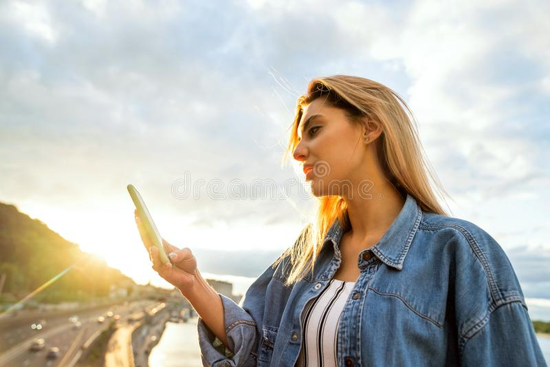 Girl freelancer working with phone at sunset stock photography