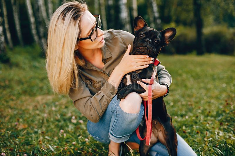 Girl with french bulldog. Pretty girl standing in a summer park. Woman with dog. Blonde in a glasses stock photography