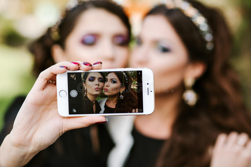 Girl friend doing a selfie. The girls at the party taking pictures of themselves on the phone. Women fashion stylish royalty free stock image