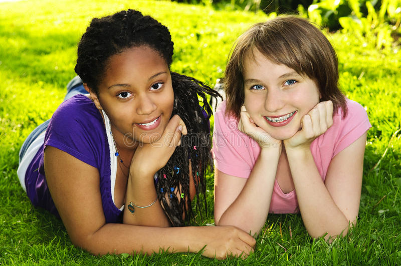 Girl friends. Two happy teenage girls laying on grass royalty free stock images