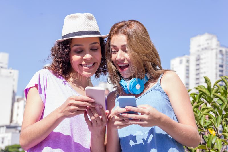 Girl friends with bright color clothing checking social media in royalty free stock photography