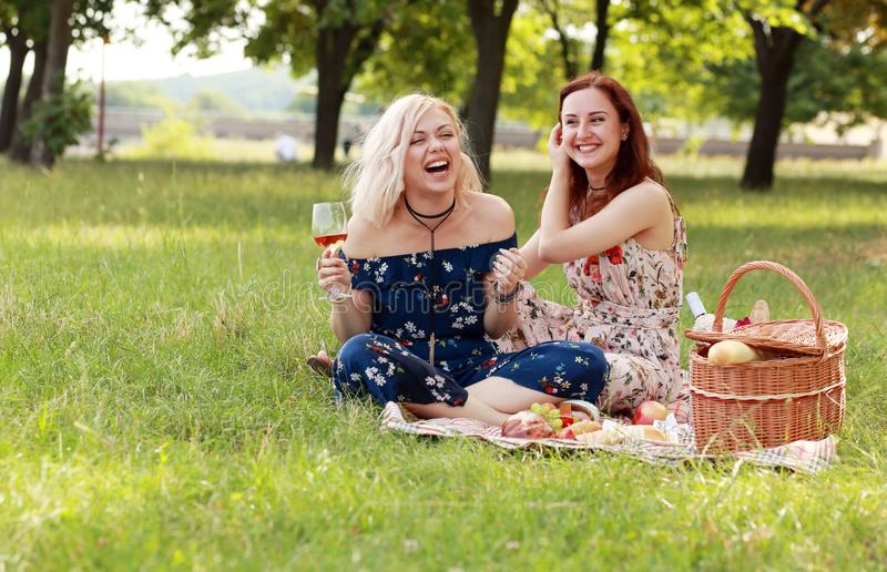 Girl friends have fun. Drink wine celebrate friendship on picnic laughing and joking royalty free stock photography