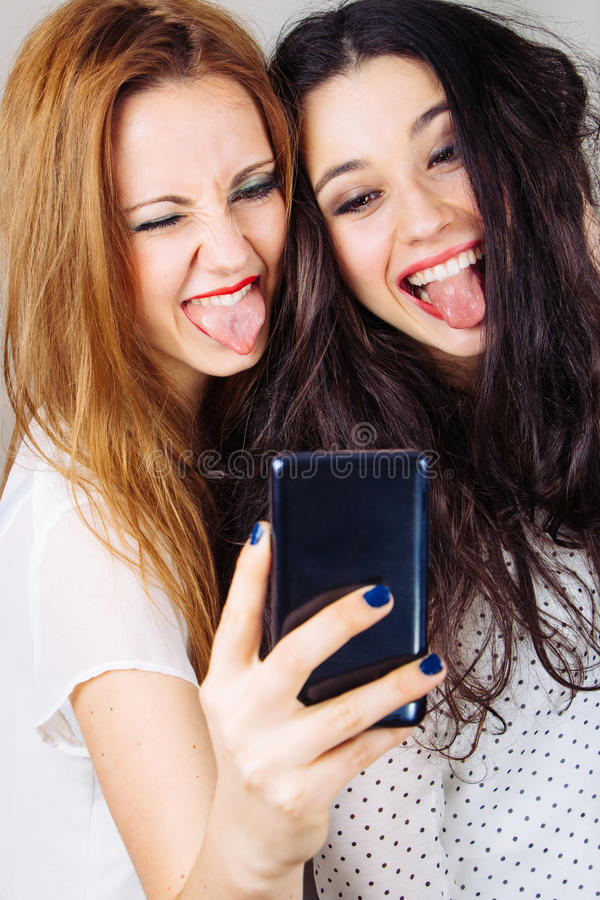 Girl friends making a funny selfie royalty free stock images