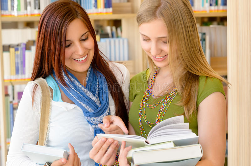 Girl friends student at high school library stock photography