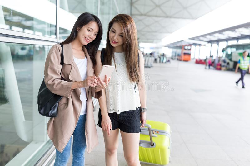 Girl friends use of cellphone at international airport. Beautiful young asian woman royalty free stock photos
